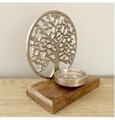 A rough luxe and beautifully intricate tree of life decoration with candle holder set upon a chunky wooden base.