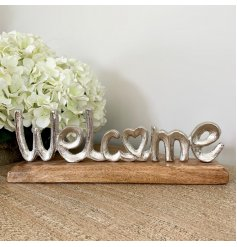 A rough luxe silver welcome sign set upon a chunky wooden base. A chic tabletop decoration for the home.