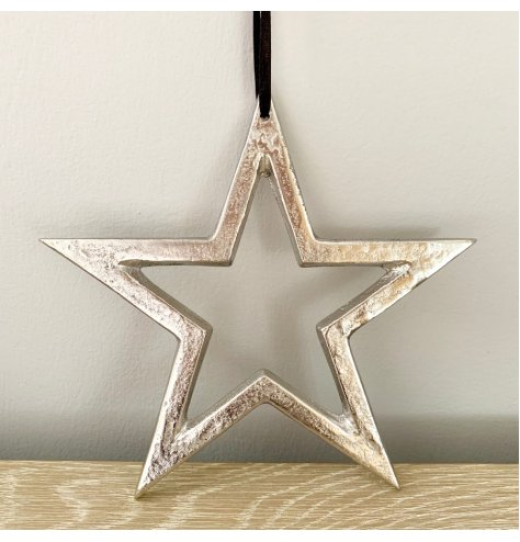 A rough luxe silver metal star with a raw, textured nickel finish. Complete with a long black ribbon hanger.