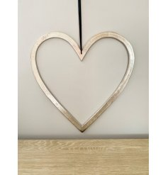 A rough luxe inspired large heart decoration with a raw nickel finish and long black ribbon hanger.