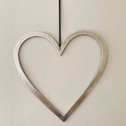 A rough luxe heart decoration with a raw nickel finish and long black ribbon hanger.