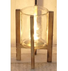 A round glass candle holder with an added natural wooden stand