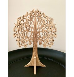 A natural wooden tree decoration with intricate carved leaves.
