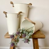 A tall cream metal vase with ridges and chunky rope handles. A much loved rustic living item.