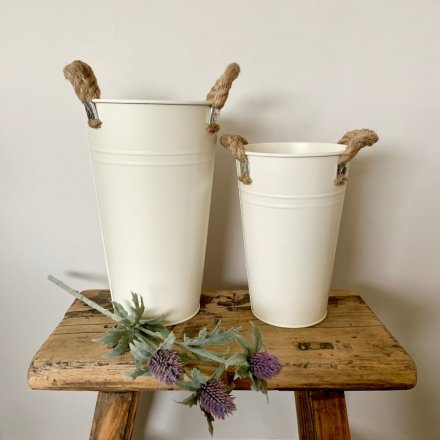 A rustic style cream vase with ridge detailing and chunky rope carry handles.