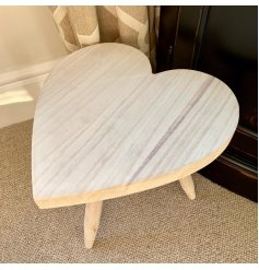 A small sized heart shaped stool complete with a smooth natural wooden feature.