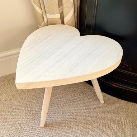 A large sized heart shaped stool complete with a smooth natural wooden feature.