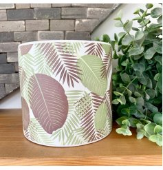 A classic white ceramic planter decorated with a colourful fern foliage print pattern.