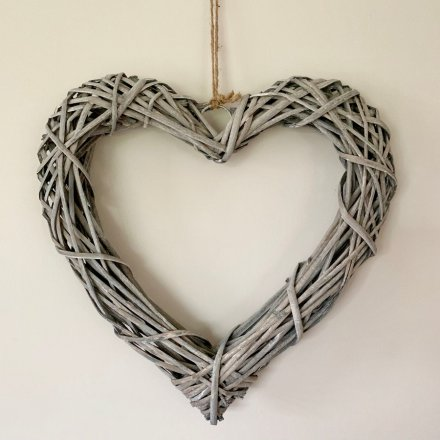 A large woven heart wreath made from natural rattan. Complete with a chunky rope hanger.