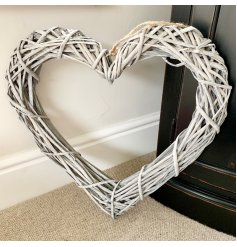 A large rustic rattan heart shaped wreath with woven branches and a chunky rope hanger.