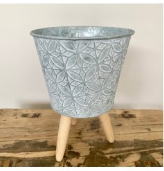 Stood on natural wooden legs, this beautifully rustic zinc pot also features a diamond embossed print