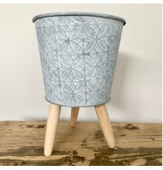 this zinc metal planter is rested upon 3 natural wooden legs and also displays a rustic charm finish