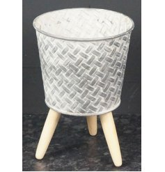Stood on natural wooden legs, this beautifully rustic zinc pot also features a geometric inspired embossed print