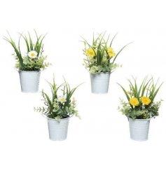 A mix of artificial blooms planted inside little white zinc bucket pots