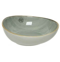 A smooth glazed porcelain bowl featuring a distressed edging and charming Sage Green tone