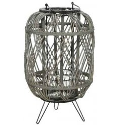 A simple and sophisticated grey rattan lantern with a woven pattern and black feet.