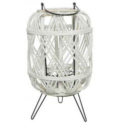 A chic white rattan lantern on feet with a rustic woven design and handle.