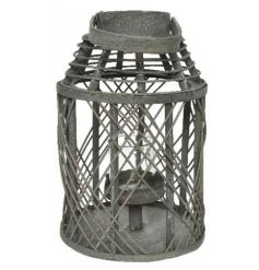 A rustic grey rattan lantern with a woven pattern and glass insert.