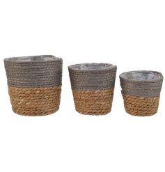 A set of 3 rustic woven baskets in assorted sizes. Each has a contemporary two-tone accessory in grey and natural colour