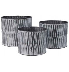 A set of 3 round zinc planters with a distressed aztec design.