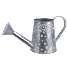 A pretty zinc watering can with a ditsy daisy floral design which cascades down the side of the product.
