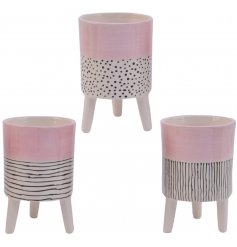 An assortment of 3 contemporary dolomite planters, each with a graphic pink, black and white design.