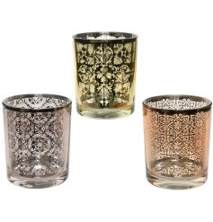 An assortment of 3 coloured candle pots, each decorated with an intricate silver toned pattern