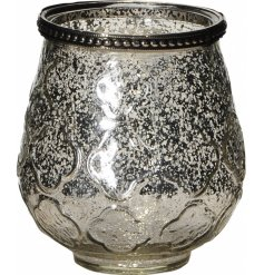 A stylish, vintage inspired glass candle holder with a mottled finish and decorative floral pattern.