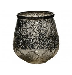 An ornate, vintage inspired glass candle holder with a repeat floral pattern and mottled finish.