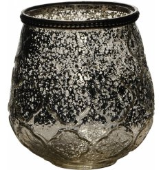 A decorative glass candle holder with an antique inspired mottled finish and geometric design.
