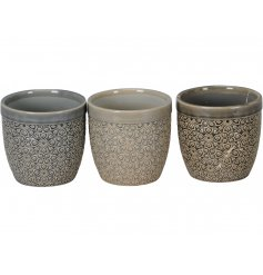 A mix of 3 glazed planters with a geometric floral design. The assortment includes subtle cream and grey designs