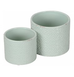 A set of 2 decorative planters with a geometric motif and distressed finish.