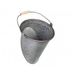 A rustic bucket planter with wooden handle, making a unique and stylish garden accessory.