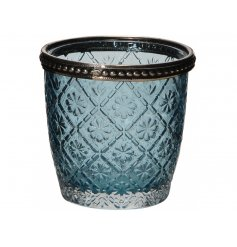 A chic blue glass votive with a floral design and decorative metal rim.