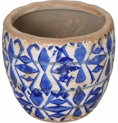 A vintage inspired garden planter with a richly glazed blue and white geometric design.