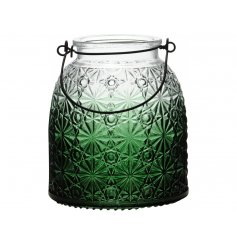 A stylish glass lantern with a decorative floral design and green ombre finish.