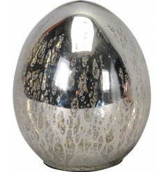 A vintage inspired decorative silver egg with a mottled, mirrored finish.