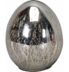 An antique inspired decorative silver egg ornament with a mirrored finish.