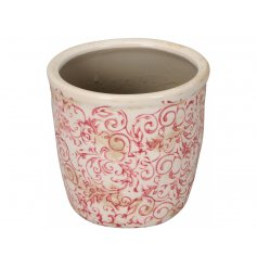 A vintage inspired planter with a rustic floral design in subtle pink hues. A distressed item with a shabby chic finish.