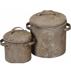 A set of 2 rustic metal pot planters with an antique finish and twin carry handles.