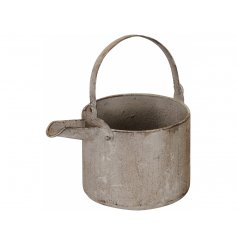 A charming rustic kettle planter with a distressed, textured finish.