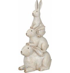 A shabby chic, whitewashed ornament featuring 3 playful climbing hares, each with pointed ears and smiling faces.