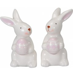 A mix of 2 pink and white Easter bunny ornaments with geometric printed eggs.