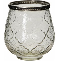An antique inspired glass t-light holder with a decorative floral design and metal rim.