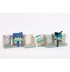 A set of 3 jewel coloured candle pots featuring a decorative peacock feather design.