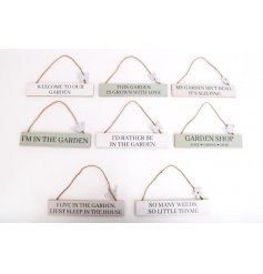 A wide assortment of sage green and white toned hanging plaques, each set with a gardening inspired text
