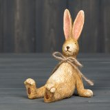 A charming and beautifully detailed sitting rabbit figure, complete with a rustic jute string bow.