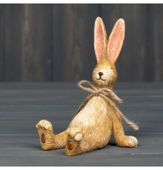 A rustic sitting rabbit decoration with charming carved details and a rustic jute bow.
