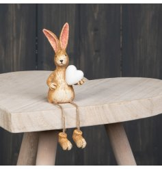 A cute little shelf sitting bunny ornament complete with a white heart and dangly legs