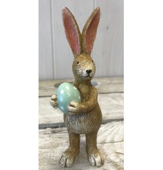 A cute little standing bunny ornament complete with a pastel green Easter Egg